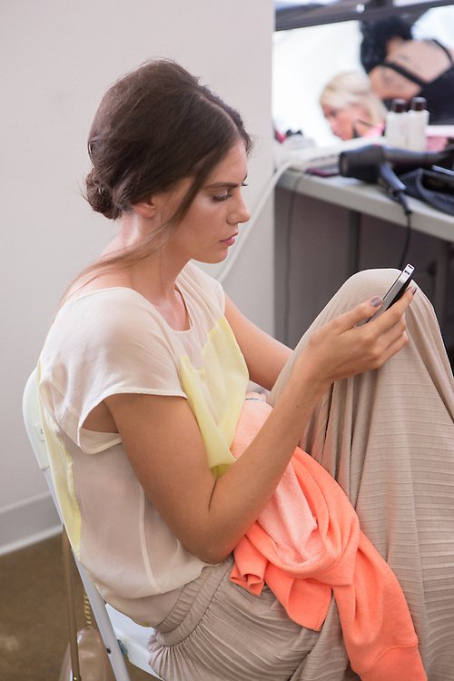 A model checks her phone as she waits backstage at the Carmen Marc Valvo Spring 2013 show at Fashion Week in New York.