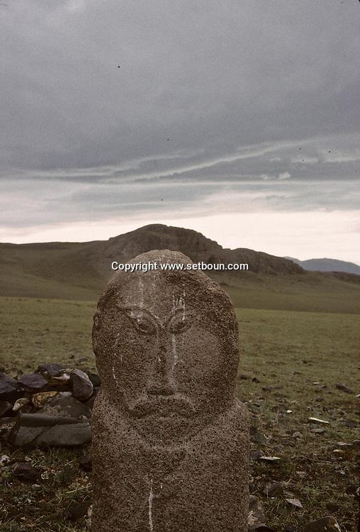 Mongolia. stone statue (Turkish 6th century)         / Statue anthropomorphe. Sum de DJARGALAN, dans l'aymag de GOV ALTAY (Granit, VI-VIIIème siecle). / Exemple de l'art monumental des nomades d'Asie Centrale, ce type de statue monolithe, représente une  - 'idole de pierre -  (KUN TCHULUU). D'après la coutume du culte des Ancêtres, cette statue était érigée à la surface d'une tombe d'un noble guerrier, à l'époque des Turcs Célestes. Leur visage présente pratiquement les mêmes caractéristiques : faciès plat, pommettes saillantes, yeux en amandes et moustache. L'idole, vêtue d'une robe avec ceinture, a le bras droit plié au niveau du coude et tient une coupe. Parfois, des oiseaux de passage viennent s'y poser.   / /5    L0006223  /  P0002610