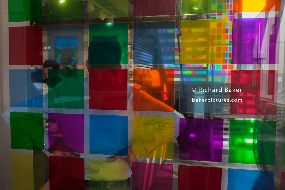 Seen through the chequered squares of a shop window, a worker on a lunch break waits to be served in the City of London, England UK.