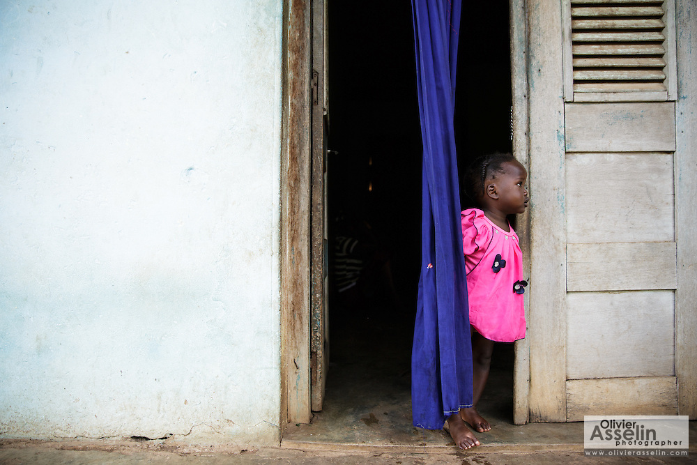 A toddler stands in the doorway of her home in Katiola, Cote d'Ivoire on Saturday July 13, 2013.
