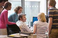 Office workers standing around colleague using computer back view