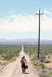 Man carrying a little boy down Route 66 in Barstow, California