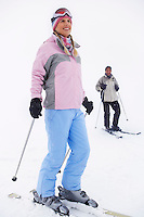 Woman skier standing on ski slope man on skis in background