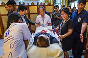 27 JANUARY 2014 - BANGKOK, THAILAND: Funeral workers bring the body of Suthin Taratin, into the funeral parlor for the bathing rites for Suthin at Wat Sommanat Rajavaravihara in Bangkok. In Thai tradition, after death a bathing ceremony takes place in which relatives and friends pour water over one hand of the deceased. Suthin was a core leader of the People's Democratic Force to Overthrow Thaksinism (Pefot), one of several organizations leading protests against the elected government of Thai Prime Minister Yingluck Shinawatra. He was murdered Sunday, Jan. 28, while he was leading a rally to prevent voters from reaching a polling center in the Bang Na district of Bangkok.     PHOTO BY JACK KURTZ