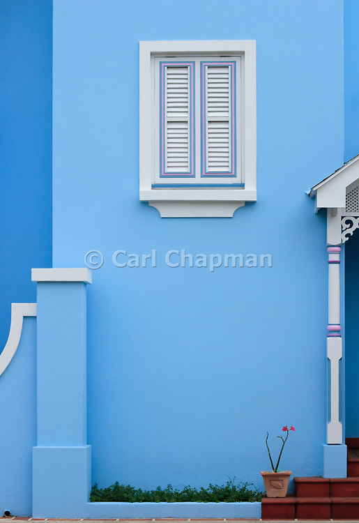 White wooden window shutter on blue house - Rockley, Barbados