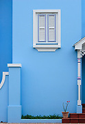 White wooden window shutter on blue house - Rockley, Barbados <br />