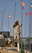 Pfc. Darrell Cole of the C Battery 1-17 Field Artillery, stands on top of a HUMVEE and scans the horizon at forward operating base Caldwell, 15 Jan 2006. To either side of him are communication antennas for SINGAR transceivers, PLUGER global positioning system, and the flat box shaped antenna for the Movement Tracking System (MTS). The MTS has additional capabilities of route navigation and secure instant messaging.  (U.S. Air Force photo by Master Sgt. Lance Cheung)<br />