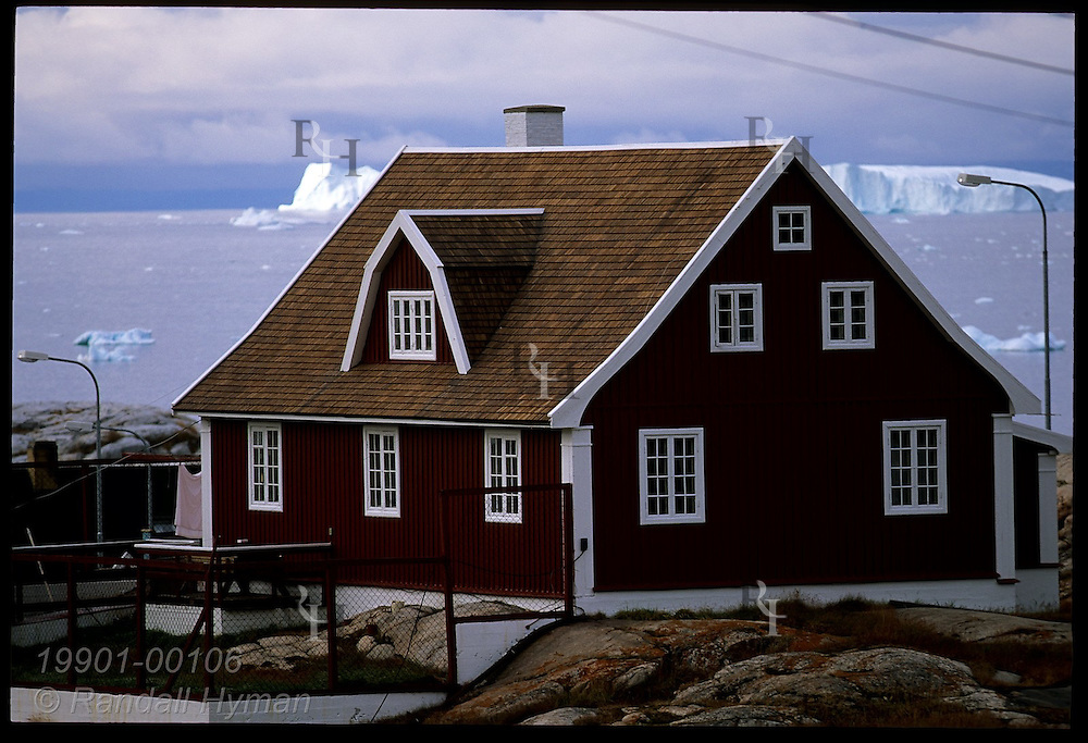 Danish-style wooden building sits on rocky hillside overlooking Disko Bay icebergs in the town of Ilulissat, Greenland.