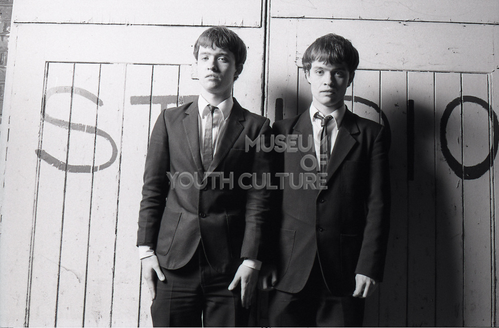 Two members of the band The Bishops standing together leaning against wall with studio written on it.