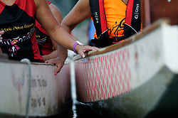 Peddlers hold onto sides of Dragon Boats used to give audience a close-up experience of the acrobatics and dance show on and above the Schuylkill River, during the Invisible river Festival. (Bastiaan Slabbers/for PhillyVoice)
