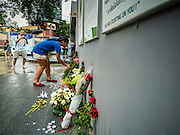 15 NOVEMBER 2015 - BANGKOK, THAILAND: A woman leaves flowers at the gate of the French Embassy in Bangkok, Thailand. Security was heightened at the embassy after terrorists attacked civilian targets in Paris, France, on Nov. 13. The terrorists, affiliated with IS/ISIL killed more than 120 people. People left flowers at the gate to the embassy.         PHOTO BY JACK KURTZ