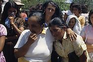 El Salvador. burial of the victims after the killing in Chalatenango; the civilian have to money to pay the coffins, the bodies are burried in a comunal grave.only the soldiers have their coffins paid by the army. The guerilla has organised an ambush on the road, 18 adults and 4 children were killed.      / enterrement des morts apres le massacre de Chalaltenango. les civils de la ville enterrent leurs morts dans une fosse commune car ils n'ont pas les moyens d'acheter un cerceuil. seuls les militaires ont droit a un cerceuil paye par l armee. La guerilla a organise une embuscade sur la route a la sortie du village, 18 civils et 4 enfants voyageant dans un bus ont ete tues    Salvador  / SALV34303 1c