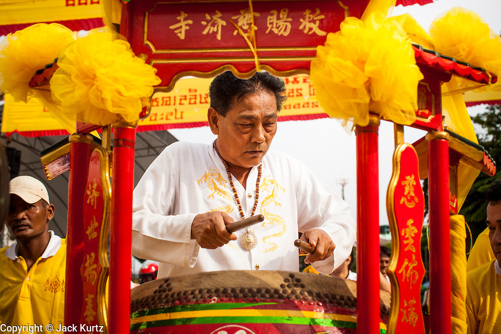14 OCTOBER 2012 - BANGKOK, THAILAND:    A Chinese drummer performs as his colleagues enter a Chinese shrine on Yaowarat Road on the first day of the Vegetarian Festival in Bangkok's Chinatown. The Vegetarian Festival is celebrated throughout Thailand. It is the Thai version of the The Nine Emperor Gods Festival, a nine-day Taoist celebration beginning on the eve of 9th lunar month of the Chinese calendar. During a period of nine days, those who are participating in the festival dress all in white and abstain from eating meat, poultry, seafood, and dairy products. Vendors and proprietors of restaurants indicate that vegetarian food is for sale by putting a yellow flag out with Thai characters for meatless written on it in red.     PHOTO BY JACK KURTZ