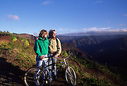 Couple biking, Waimea Canyon, Kauai, Hawaii<br />