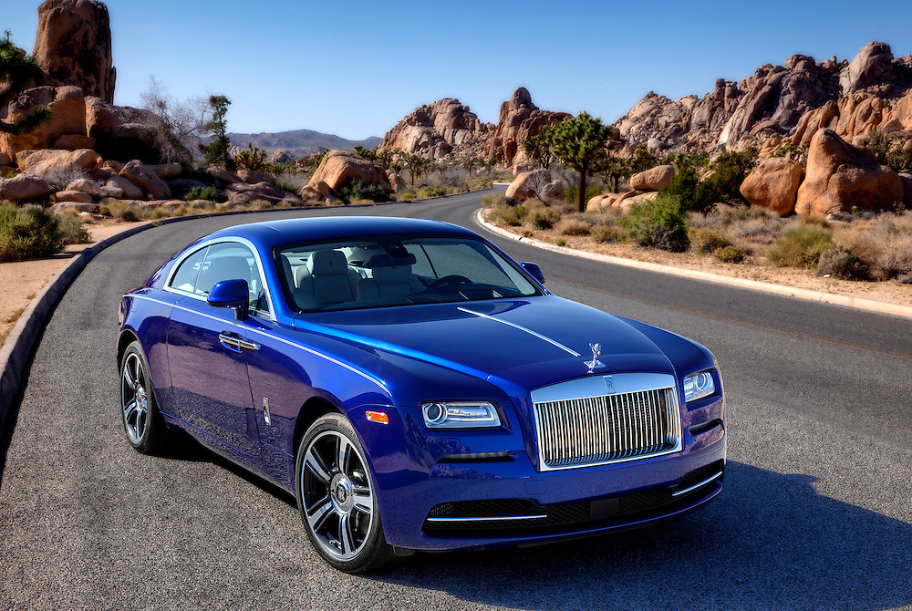 2015 Rolls Royce Wraith, Salamanca Blue.  Photographed in Joshua Tree, CA. 3/4 front view on a paved windy road.