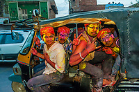 Men riding an auto rickshaw leaving the Lathmar Holi (Holi, Festival of Colors), Barsana, near Mathura, Uttar Pradesh, India.