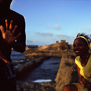 A man claps while singing to women on the reef outside the Malecon, a seawall and embankment that runs up the coast of Old Havana, Cuba. On weekends, the Malecon is a famously social place, with elder walking dogs, roadside vendors, and teenagers in various stages of making-out.