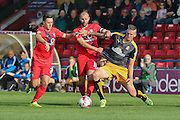 York City midfielder Russell Penn and York City forward, on loan from Oldham Athletic, Rhys Turner grapple with Cambridge United forward Liam Hughes  during the Sky Bet League 2 match between York City and Cambridge United at Bootham Crescent, York, England on 3 October 2015. Photo by Simon Davies.