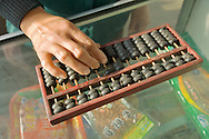 Abacus counting machine calculator. Woman hand using abacus adding subtracting sum on shop counter in Chinese shop, China