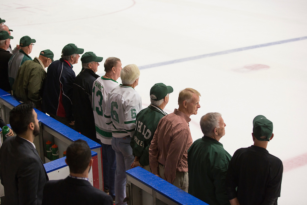 Alumni from the 1960s hockey team line up on the ice after the first period of the OU vs. Kent State hockey game in Bird Arena on September 30, 2016.