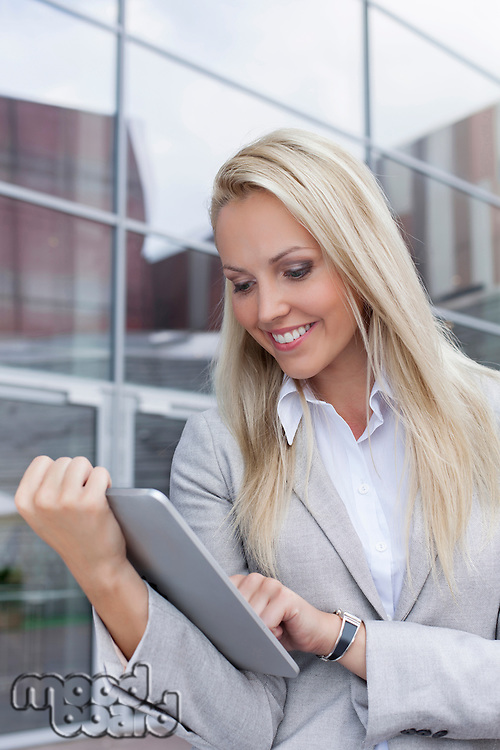 Happy beautiful businesswoman using digital tablet against office building