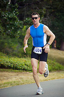 Mid 30's Caucasian man running the final stage of a triathlon.<br />