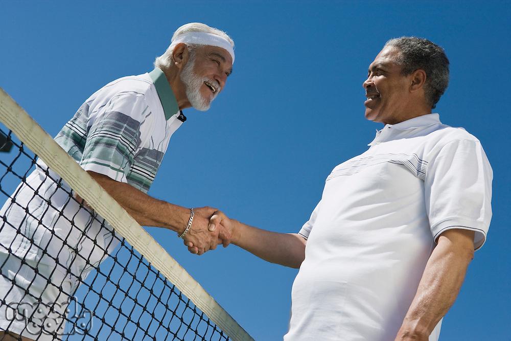 Two men shaking hands over tennis net
