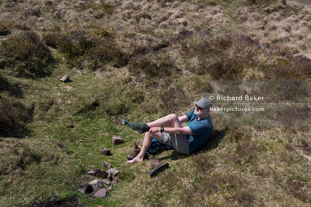 A walker put socks back on after cooling his feet on a warm day at Rowberrow on Burrington Combe, 20th April 2019 near Langford, North Somerset, England.