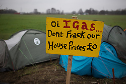 "© Licensed to London News Pictures . 24/01/2014 . Barton Moss Road , Manchester , UK . Sign reading "" Oi IGAS...don't frack our house prices £0 "" in front of tents pitched at the protest site . Site of a protest camp on Barton Moss Road where anti-fracking demonstrators are based on an access road leading to an iGas fracking site as today (24th January 2014) Greater Manchester Police announce two further arrests from the ongoing protest after reporting that a security guard was threatened and assaulted on Barton Moss Road on Monday (20th January 2014) . Photo credit : Joel Goodman/LNP"