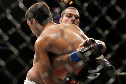October 24, 2009; Los Angeles, CA; USA; Lyoto Machida (black trunks) is held by Mauricio Rua(white trunks) during their UFC light heavyweight championship bout at UFC 104.   Machida won via controversial unanimous decison .  Mandatory Credit:  Ed Mulholland