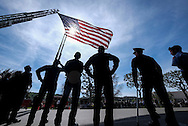 Police and firefighters stand beneath a giant U.S. flag over the processional route during the funeral of Whittier Police Officer Keith Boyer at Rose Hills Memorial Park in Whittier, Calif., Friday March 3, 2017. Boyer, who was fatally shot after responding to a traffic crash, was remembered today by thousands of law enforcement officers, friends and family as a dedicated public servant, talented drummer, loving friend and even a ``goofy'' dad.(Photo by Ringo Chiu/PHOTOFORMULA.com)<br />