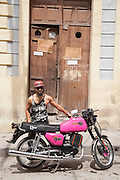 A man with his german-made MZ ETZ 250 motorbike on the street in Santiago de Cuba, Cuba