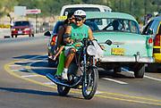 HAVANA, CUBA - OCTOBER 21, 2006: Unidentified people ride motorbike by Malecon avenue in Havana, Cuba.
