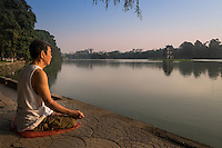 HANOI, VIETNAM - CIRCA SEPTEMBER 2014:  A Vietnamese man meditates early morning in the Hoan Kiem Lake, in Hanoi.