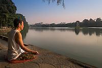 HANOI, VIETNAM - CIRCA SEPTEMBER 2014:  A Vietnamese man meditates early morning in the Hoan Kiem Lake, in Hanoi.