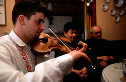 CZECH REPUBLIC MORAVIA BANOV APR98 - Jan Chovanec (L) plays the violin for his elderly hosts Helena and Josef Vystrcil at their home.  During Easter, folklore dress, music and mutual visits are part of the customary traditional celebrations in Moravia.  jre/Photo by Jiri Rezac<br />