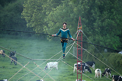 © Licensed to London News Pictures. 27/05/2017. Bruton, UK. Chis Bullzini walks a tightrope at sunset as revellers attend the Shindig Weekender festival in Bruton, Somerset on a warm and sunny weekend.. Photo credit: Jason Bryant/LNP