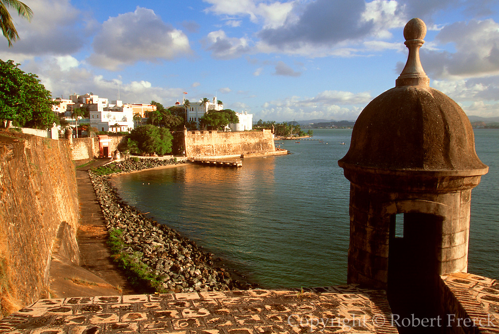 PUERTO RICO, SAN JUAN World Heritage Site, city walls and San Juan Gate on the bay, with La Fortaleza mansion above the walls (center)