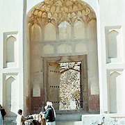25 November 1976<br /> Kabul. Elaborate honeycomb pattern on interior of domed ceiling. Metal studded doorway. Recessed niches with pointed aches in outer wall to either side. Group with donkey stands at entrance steps.