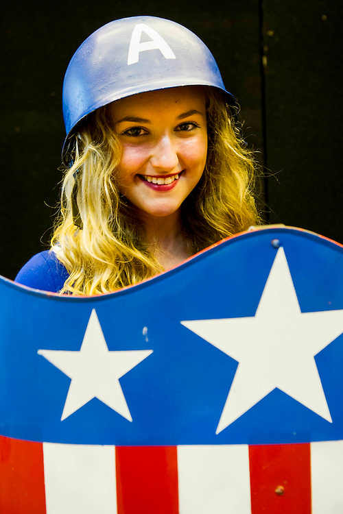 Three school friends travel down from the North East, driven by one of the fathers - Allana Kennerly, 14 from Durham, plays Captain America (pictured); Maria henry, 15 from teeside, plays Kick Ass; and Georgina Hugill, 14 from Northallaton, plays Hawkeye from the Avengers. London Film and Comic Con 2014, (LFCC), at Earls Court, London, UK.