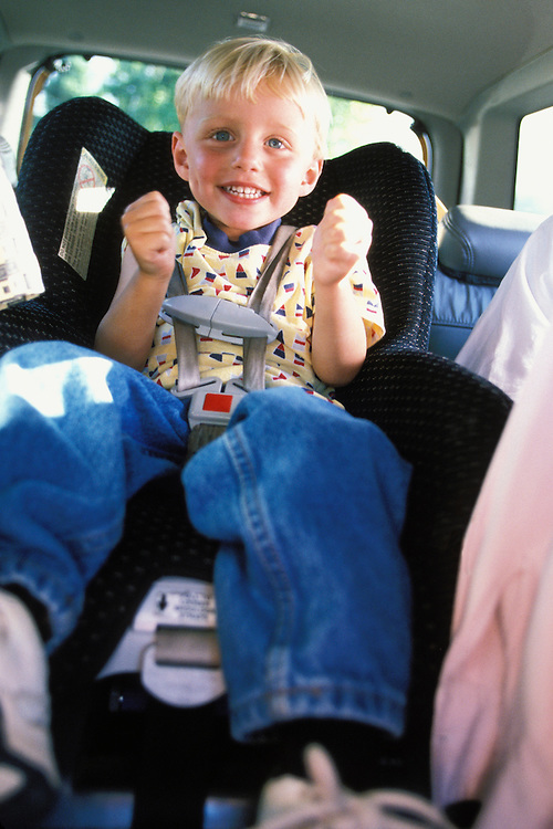 A 4 year old boy in a car seat in the back of a car.