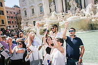 """ROME, ITALY - 20 JUNE 2017: Tourists throw coins in the Trevi Fountain in Rome, Italy, on June 20th 2017.<br /> <br /> The warm weather has brought a menacing whiff of tourists behaving badly in Rome. On April 12, a man went skinny-dipping in the Trevi fountain resulting in a viral web video and a 500 euro fine.<br /> <br /> Virginia Raggi, the mayor of Rome and a national figurehead of the anti-establishment Five Star Movement,  issued an ordinance involving harsher fines for eating, drinking or sitting on the fountains, for washing animals or clothes in the fountain water or for throwing anything other than coins into the water of the Trevi Fountain, Bernini's Four Fountains and 35 other city fountains of artistic or historic significance around the city.  """"It is unacceptable that someone use them to go swimming or clean themselves, it's an historic patrimony that we must safeguard,"""" Ms. Raggi said."""
