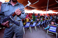 KABUL 25 August 2005..An Afghan Security Officer looks after the children who are enjoing a show organized by SOA...On 23-25 August 2005, Special Olympics Afghanistan held its first national Games at Olympic Stadium in Kabul. More than 300 athletes, including 80 female athletes, experienced a taste of happiness and achievement for the first time in their lives. They competed in athletics, bocce and football (soccer). Because of cultural restrictions, males and females competed at separate venues.