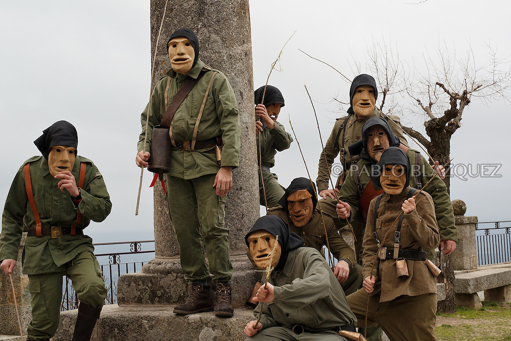 The Machurreros from Pedro Bernardo stand in a park during Carnival on February 6, 2016 in Pedro Bernardo, in Avila province, Spain. The origins of this pagan festival are unknown. The Machurreros wear wood masks, a military dress, black handkerchief, cowbells, and hold wicker stick. The festival disappeared after Dictator Franco forbid carnival festivals in 1937, but it was recently recovered. Before disappearing, male villagers after the military service, used to dress as Machurreros as they run along the streets scaring children and adults with their wicker stick to bring fertility to the land and expel the evil spirits. (© Pablo Blazquez)