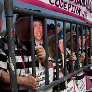 Supporters of Bradley Manning hold up pictures of his face and stand behind mock prison bars during a protest against his imprisonment near Quantico Marine Corps base, March 20, 2011. More than two dozen people were arrested during the protest, including Daniel Ellsberg, a former military analyst. The arrests came at the end of a largely peaceful demonstration.