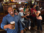 A group of friends celebrate happy hour with a cold beer and cocktails at a bar in Arlington, Texas.
