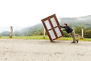 Man carries wardrobe along a mountain road