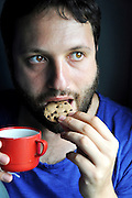 young man eats chocolate chip cookie and drinking coffee model release available