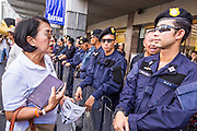 "09 JUNE 2013 - BANGKOK, THAILAND: A Thai woman who is a member of the White Masks, confronts Thai riot police during a protest against the government of Yingluck Shinawatra at Central World. The White Mask protesters wear the Guy Fawkes mask popularized by the movie ""V for Vendetta"" and the protest groups Anonymous and Occupy. Several hundred members of the White Mask movement gathered on the plaza in front of Central World, a large shopping complex at the Ratchaprasong Intersection in Bangkok, to protest against the government of Thai Prime Minister Yingluck Shinawatra. They say that her government is corrupt and is a ""puppet"" of ousted (and exiled) former PM Thaksin Shinawatra. Thaksin is Yingluck's brother. She was elected in 2011 when her brother endorsed her.     PHOTO BY JACK KURTZ"