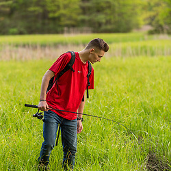 A teenage boy looks for a fising spot next to Smelt Brook in York, Maine.